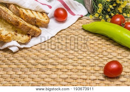 Toasted Bread In White Cloth On Straw Place Mat With Cherry Tomatoes, Green Pepper, And Flowers