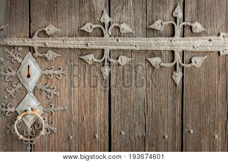 Close up of beautiful old ancient lock with metal ornament decoration on weathered brown wooden door. Horizontal composition.
