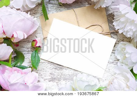 blank greeting card and envelope in frame of pink and white peonies and roses over white wooden background. flat lay. top view with copy space. wedding invitation