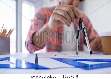 Male architect working on blueprint over drafting table in office