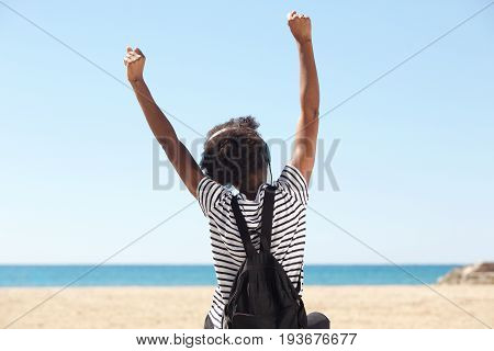 Young Woman Sitting By The Beach And Enjoining Music On Headphones