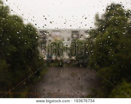 rain drops on glass street views green trees