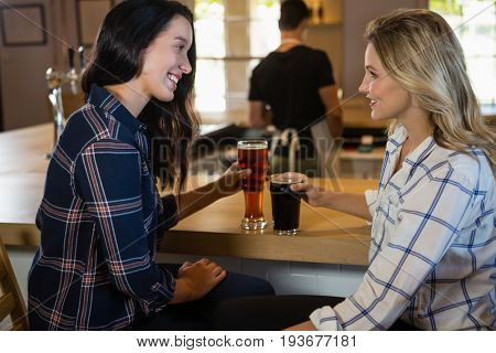 Smiling female friends enjoying drinks with bartender in background at restaurant