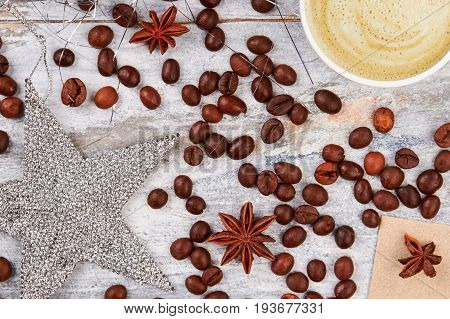 Coffee decorations on wooden background. Silver star and coffee beans. Coffe and festive mood.