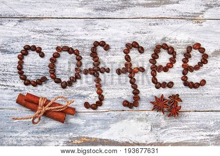 Coffee beans and spices. Cinnamon and badian on wooden background. Coffee symbol of good mood.