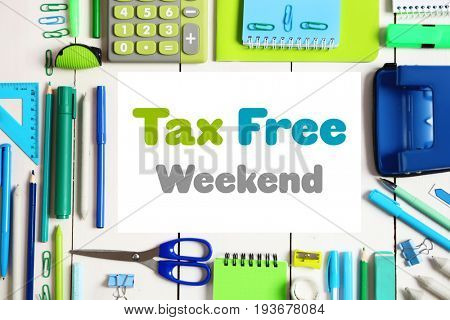 Office supplies and paper with text TAX FREE WEEKEND on wooden background