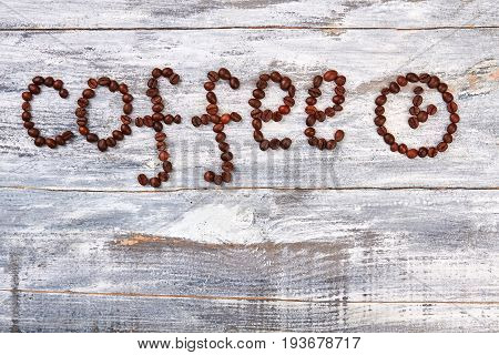 Clock from coffee on table. Coffee bean on wooden background.