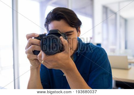 Male executive clicking a picture on digital camera in office