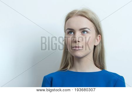 Woman with adorable face and long blond hair posing in blue dress. Girl with makeup foundation on healthy skin on white background. Visage cosmetics skincare make up. Beauty youth copy space