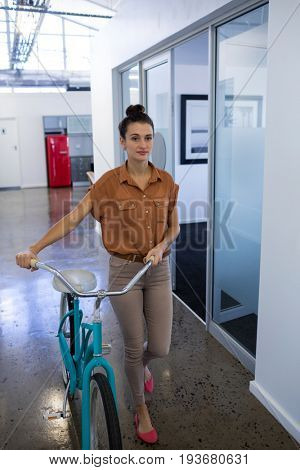 Female executive walking with bicycle in the office corridor