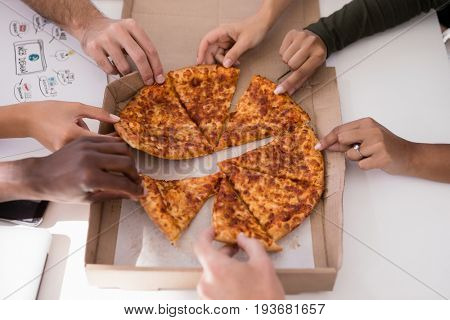 Close-up of executives sharing pizza in office