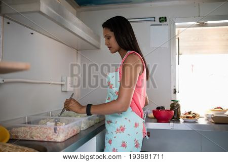 Attentive waitress preparing food in food truck