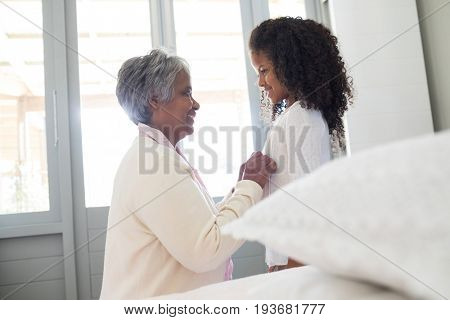 Grandmother dressing up her granddaughter in bedroom at home