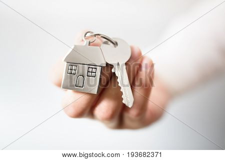 Holding house keys on house shaped keychain concept for buying a new home