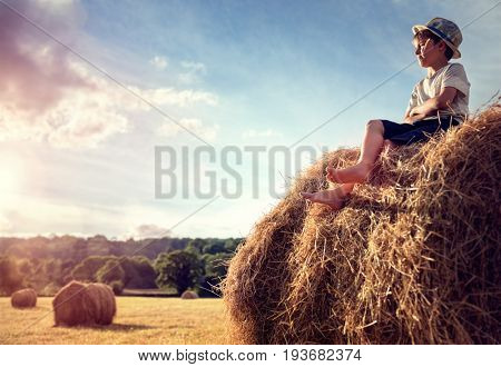 Boy sitting on a haystack in summer watching the sunset
