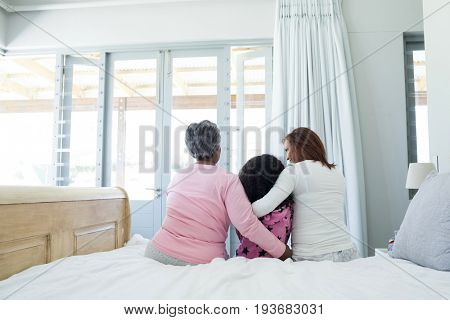 Rear view of family sitting together with arm around on bed in bedroom