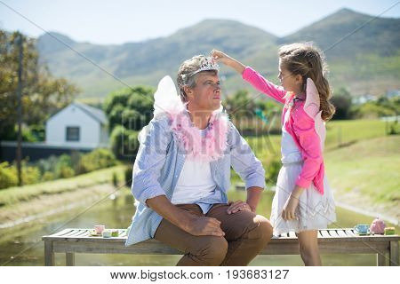 Daughter in angel costume adjusting crown on father head at garden