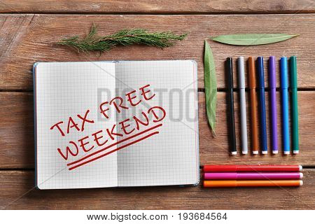 Notebook with text TAX FREE WEEKEND and felt-tip pens on wooden background