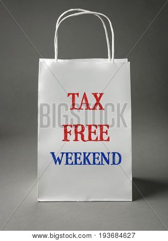 Paper bag with text TAX FREE WEEKEND on gray background
