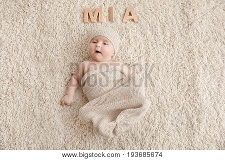 Cute baby with word MIA lying on carpet. Choosing name concept