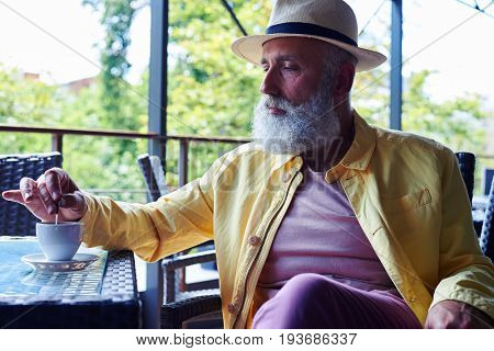 Elderly man sitting in cafe on chair looking seriously, holding spoon in hand, wearing yellow jacket, mid shot