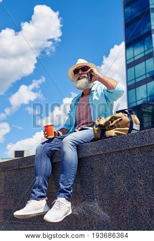 Side view of bearded man sitting and talking by phone enjoying time outdoors on sunny day, bag next to him, mid shot