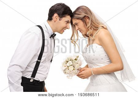 Furious newlywed couple pushing their heads against each other isolated on white background