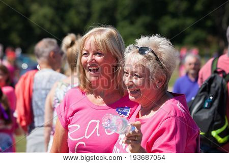 SOUTHAMPTON UK - July 2 2017: Race for Life women run and walk to raise money for Cancer Research charity in Southampton UK. Friends smiling having finished the run to raise money.