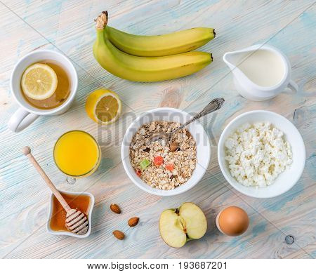 Organic vegetarian breakfast with oatmeal and fruits, hot tea with lemon, orange juice, topview