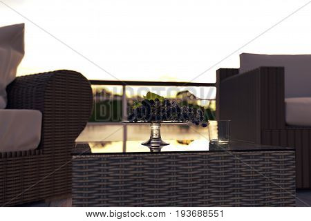 3d rendering of glass bowl with grapes in front of blurred rattan furniture and lake in the evening sunshine