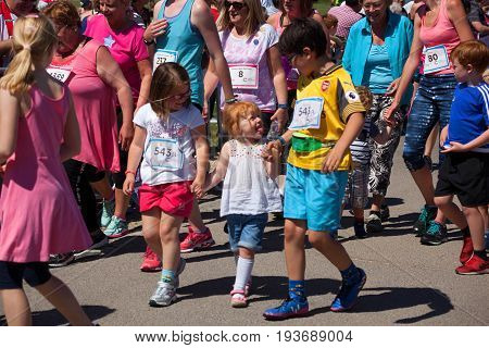 SOUTHAMPTON UK - July 2 2017: Race for Life women and children run and walk to raise money for Cancer Research charity in Southampton UK. Children walking amongst women to raise money for charity. Playing and pulling funny face.