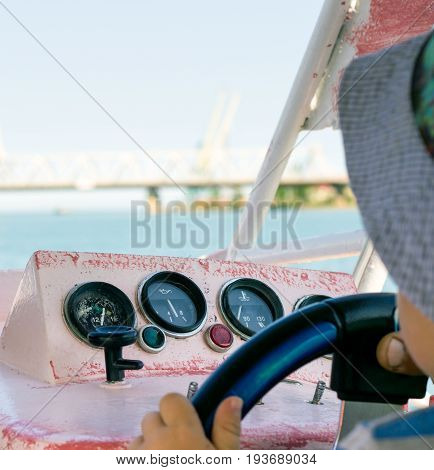A small boy swims by the sea on a boat he holds the helm in front of him a view of a beautiful bridge over the water