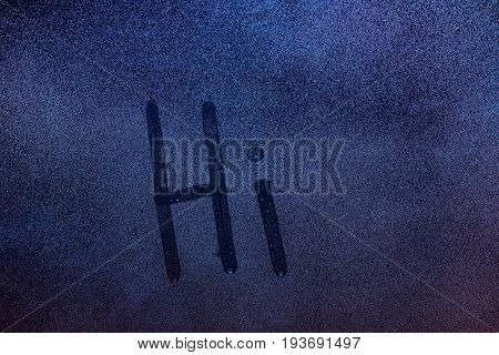 Hi word draw on wet window glass. Hi message on frozen window background