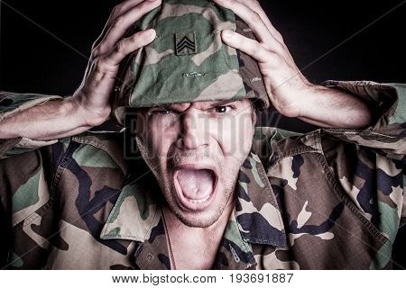 Scared military man holding helmet screaming