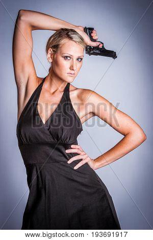Beautiful sexy female spy holding gun