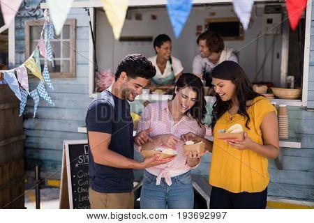 Smiling friends eating snacks in food truck van