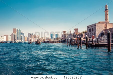 Skyline View Of Dubai Creek With Traditional Boats And Piers. Sunny Summer Day. Famous Tourist Desti