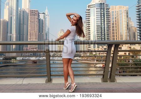 Happy Beautiful Tourist Woman In Fashionable Summer White Dress Walking And Enjoying In Dubai Marina