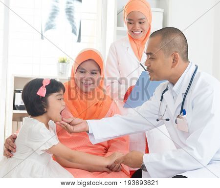 Southeast Asian male doctor examining little girl patient. Muslim medical concept.