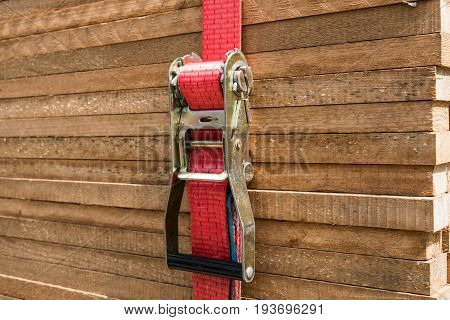 red ratchet strap fixing wood boards / wooden planks / stacked tables