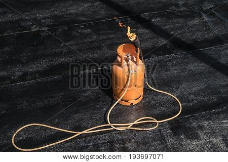 Orange butane gas tank with flame torch on the floor with bituminous waterproofing mambrane sheets