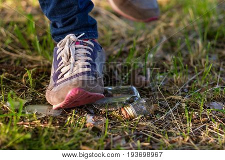 Woman going on the grass in sneakers. Risk of stepping on a splinter of broken bottle glass.