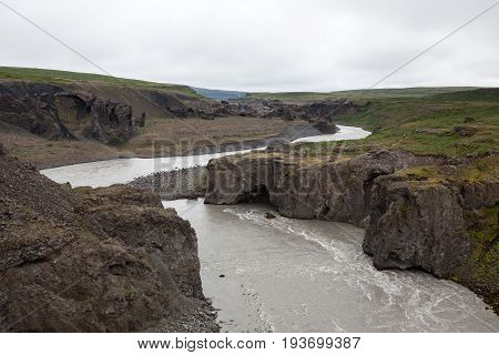 Iceland River Landscape On A Gray Cloudy Day. River Surrounded By Big Cliffs. Deep Grey River Near A