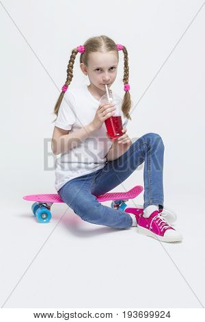 Kids Concepts. Portrait of Little Caucasian Blond Girl with Long Pigtails Posing With Pink Pennyboard and Drinking Red Juice with Straw. Against White. Vertical Image Composition