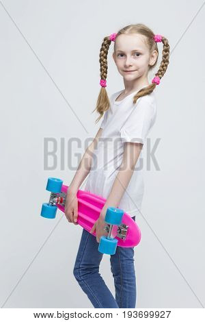 Kids Concepts and Ideas. Little Caucasian Blond Girl with Nice Pigtails Posing With Pink Pennyboard Against White Background. Vertical Shot