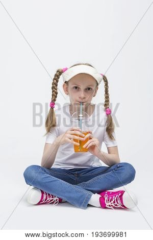 Kid Ideas and Concepts. Portrait of Pretty Caucasian Blond Girl wearing Visor Sitting on Floor with Cup of Juice and Drinking Through Straw. Vertical Image