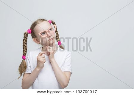 Portrait of Thinking Caucasian Blond Girl With Pigtails Posing with Artistic Spectacles Against White Background. Horizontal Image