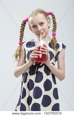 Portrait of Funny and Curious Smiling Caucasian Girl With Pigtails Standing in Polka Dot Dress with Cup of Red Juice. Against White. Drinking Through Straw.Vertical image