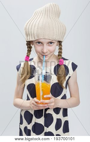 Portrait of Funny Caucasian Girl With Pigtails Posing in Warm Hat and Polka Dot Dress with Cup of Orange Juice. Drinking Through Straw. Against White. Vertical image Composition