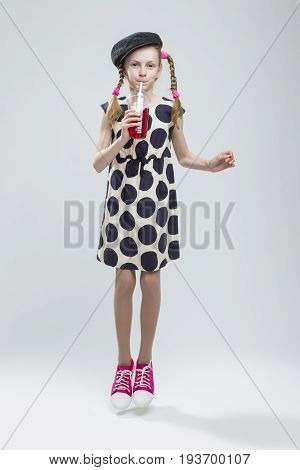 Full Length Portrait of Jumping Caucasian Girl With Pigtails Posing in Gray Velvel Cap and Polka Dot Dress with Cup of Red Juice. Drinking Through Straw. Against White. Vertical Shot Composition